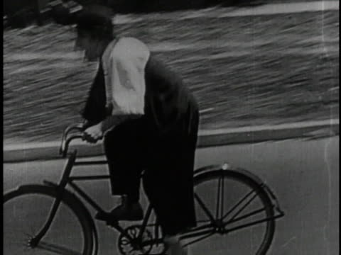 1920 montage man uses bicycle then motorcycle to chase car containing villains and abducted woman  - larry semon stock videos and b-roll footage