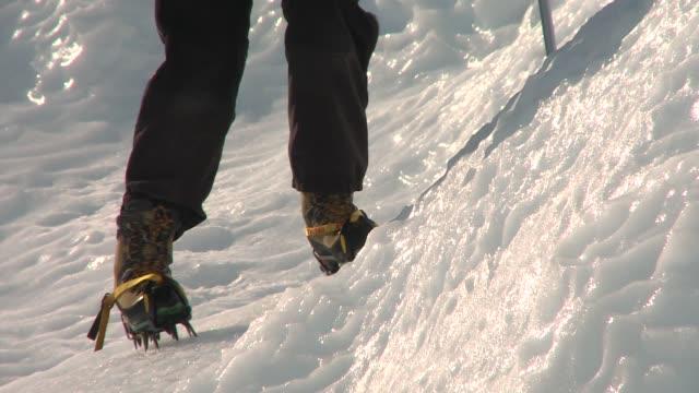 vídeos y material grabado en eventos de stock de a man uses crampons to dig into the ice as he climbs. available in hd. - artículo de montañismo