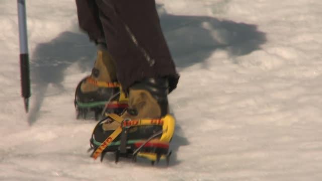 vídeos y material grabado en eventos de stock de a man uses crampons to dig into the ice as he hikes. available in hd. - artículo de montañismo