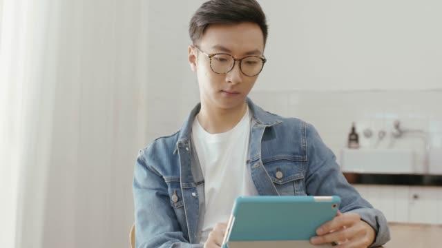 Man uses digital tablet at home (slow motion)