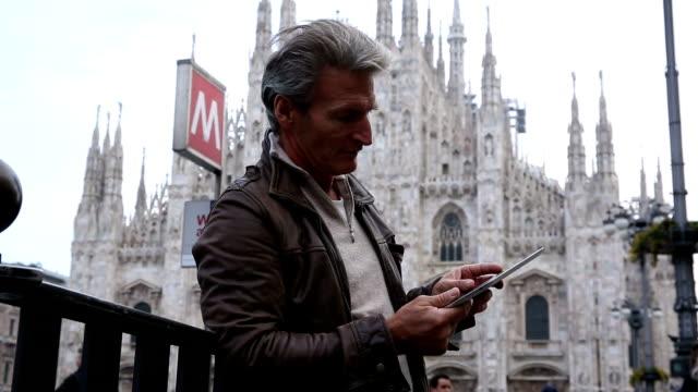 Uomo utilizza digital tablet, davanti al Duomo, Milano, Italia