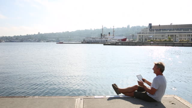 man uses digital tablet, on urban pier - technophile stock videos & royalty-free footage