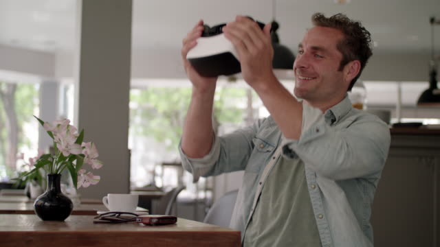 man uses his hi-end VR-headset in a coffeehouse