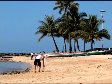 男は彼のビーチでのメダル検出器 - 宝探し点の映像素材/bロール