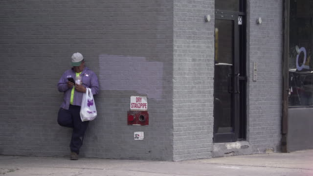 Man uses his phone while leaning against side of building in Brooklyn.