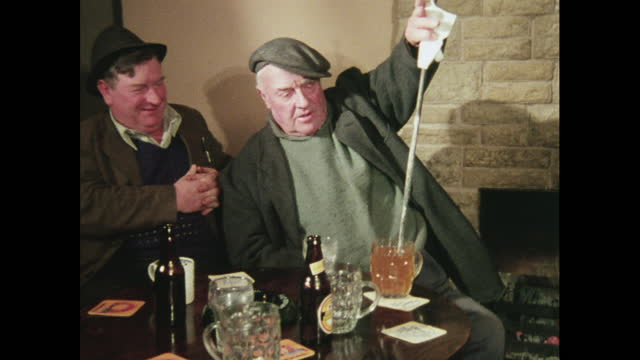 man uses hot poker to heat drink, 1970s - beer bottle stock videos & royalty-free footage