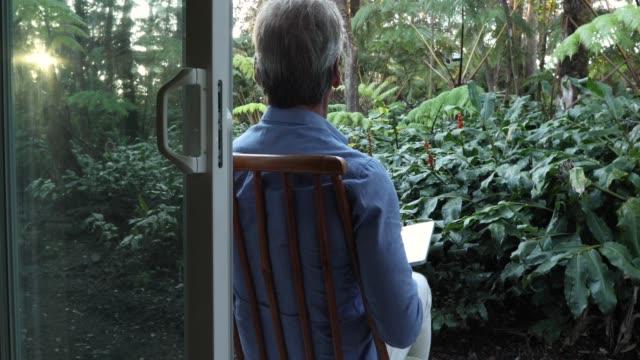 Man maakt gebruik van laptop computer, kijkt uit in jungle omgeving