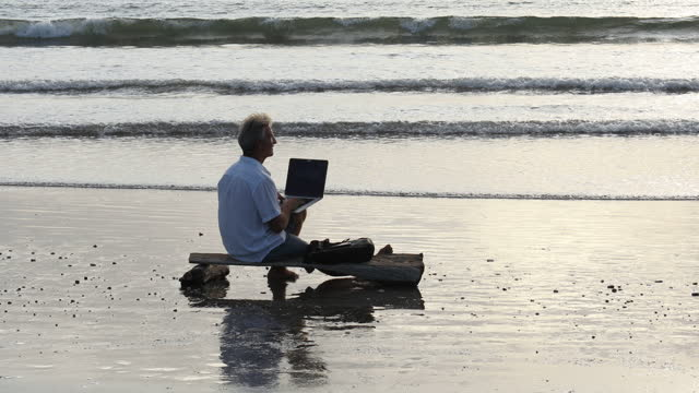 man uses laptop computer while sitting on makeshift bench - solitude stock videos & royalty-free footage