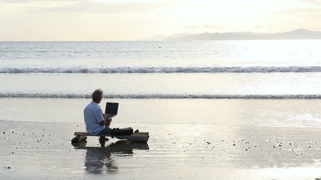 man uses laptop computer while sitting on makeshift bench - using laptop stock videos & royalty-free footage