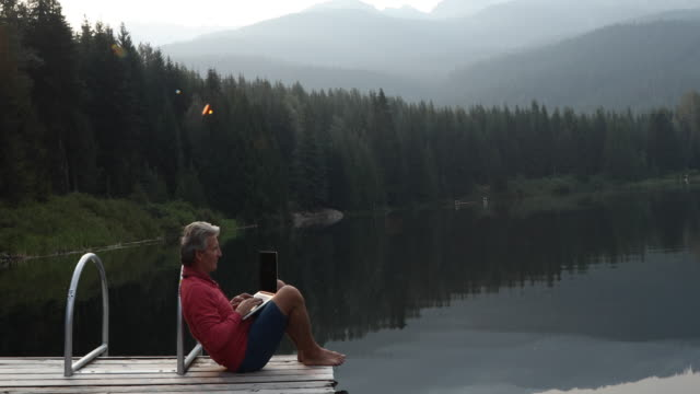 Man uses laptop computer while sitting on pier at sunrise
