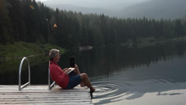 日の出桟橋に座ってノート パソコンを使う - 中年の男性だけ点の映像素材/bロール