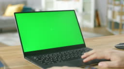 Man Uses Laptop with Green Mock-up Screen While Sitting at the Desk in His Cozy Living Room.
