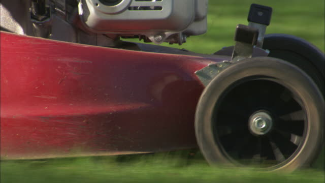 Man uses lawnmower in garden, Scotland, UK