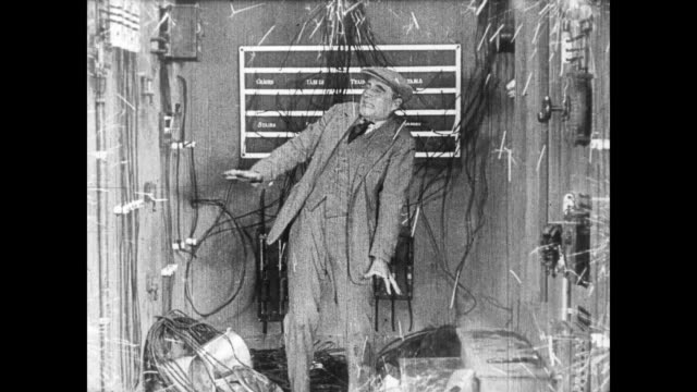 1922 man (buster keaton) uses pots and pans to electrify bad guy - silent film stock videos & royalty-free footage