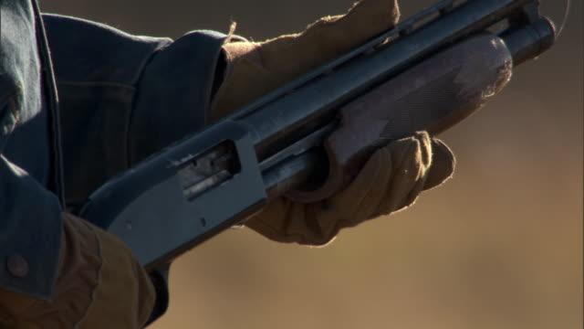 Man uses pump action on shotgun, Yellowstone, USA
