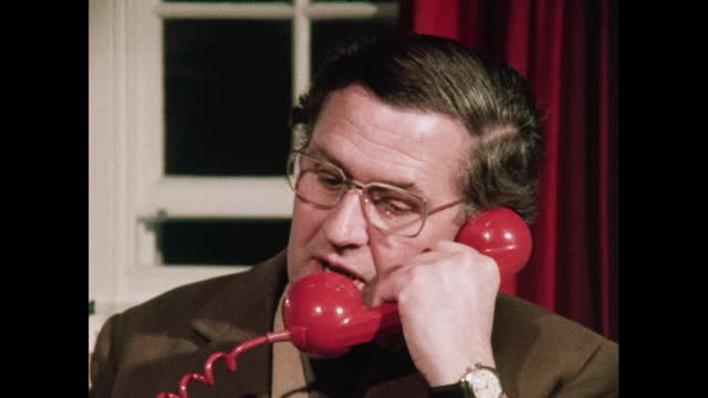 man uses red rotary phone, 1970s - answering stock videos & royalty-free footage