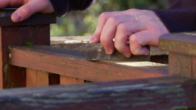 man uses sanding block on wooden decking - terrazza in legno video stock e b–roll