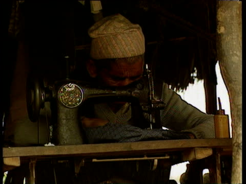 man uses sewing machine in nepalese village - nepal stock-videos und b-roll-filmmaterial