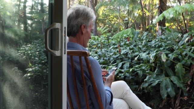 Man maakt gebruik van slimme telefoon, kijkt uit in jungle omgeving