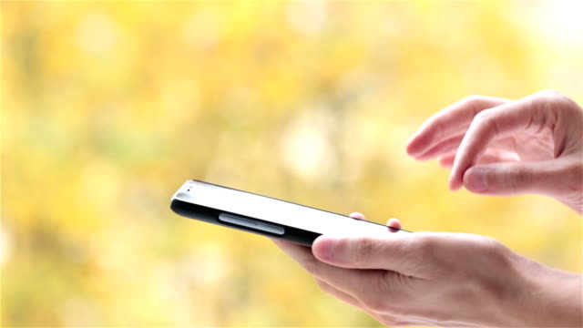 Man uses smartphone on background of yellow leaves.