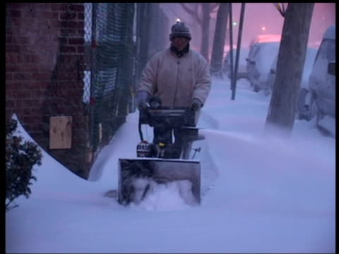 man uses snow blower to clear pavement at twilight, queens, new york - veicolo di terra per uso personale video stock e b–roll