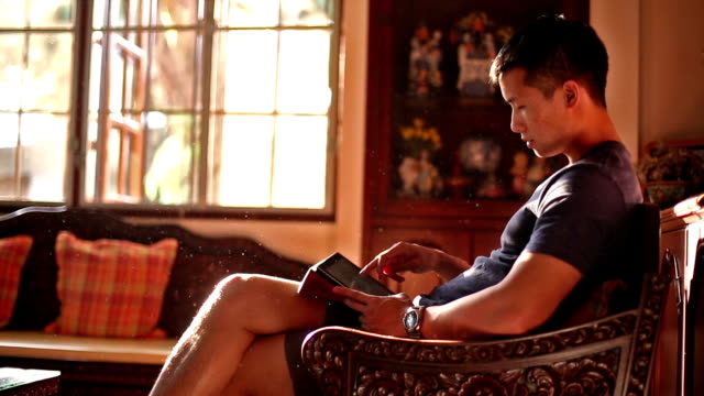 man uses tablet sitting on wooden chair - young men stock videos & royalty-free footage