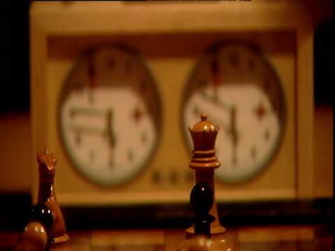man uses white pawn to take black pawn in game of chess and focus pulls to chess clock in background - chess stock videos & royalty-free footage
