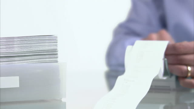 Man using a calculator next to him a pile of paper decreasing and increasing Sweden.