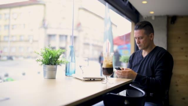 vídeos de stock, filmes e b-roll de homem que usa um telefone de pilha ao sentar-se em uma barra, emitindo mensagens de texto - one young man only