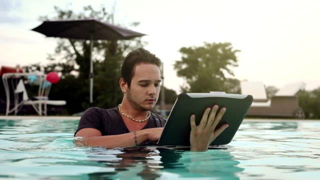 Man using a damaged malfunctioning laptop in swimming pool