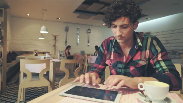 man using a digital in a cafeteria. - youth unemployment stock videos & royalty-free footage