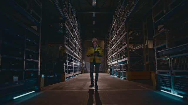 stockvideo's en b-roll-footage met slo mo man met behulp van een digitale tablet tijdens het lopen in het magazijn - buiten de vs