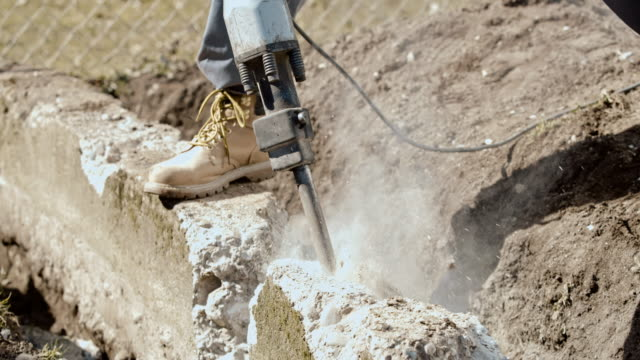 slo mo man using a jackhammer to break up concrete block in the backyard - only men stock videos & royalty-free footage