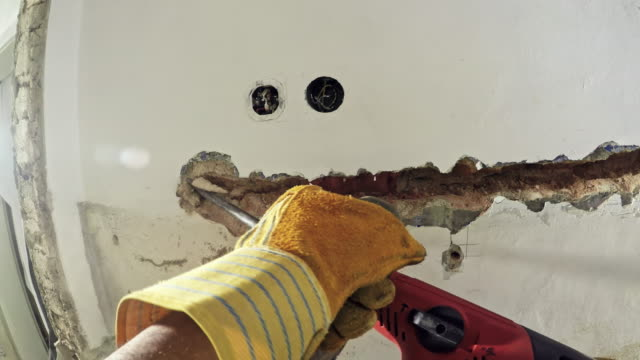 POV Man using a jackhammer to tear down a wall in the house