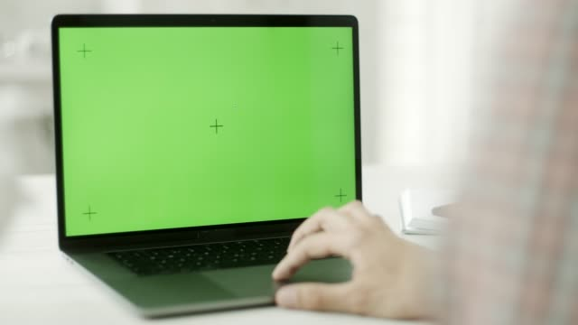 vídeos de stock e filmes b-roll de a man using a laptop with a green screen - monitor de computador