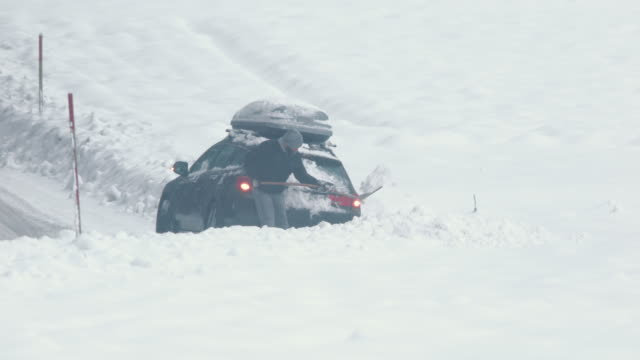 Man using a large shovel to dig his car out of snow