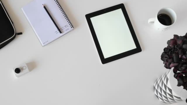 a man using a mobile phone and then working on his tablet with finger gestures on a blank screen, at a white black themed desktop set-up - blank screen stock videos & royalty-free footage