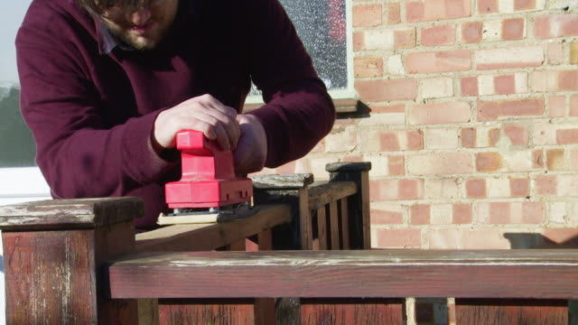 man using a power sander - terrazza in legno video stock e b–roll