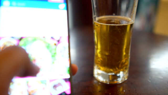 man using a smart phone while drinking a beer - bar drink establishment stock videos and b-roll footage