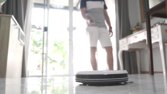 vídeos de stock, filmes e b-roll de homem usando um smartphone controlando um aspirador robótico inteligente em casa - conveniência