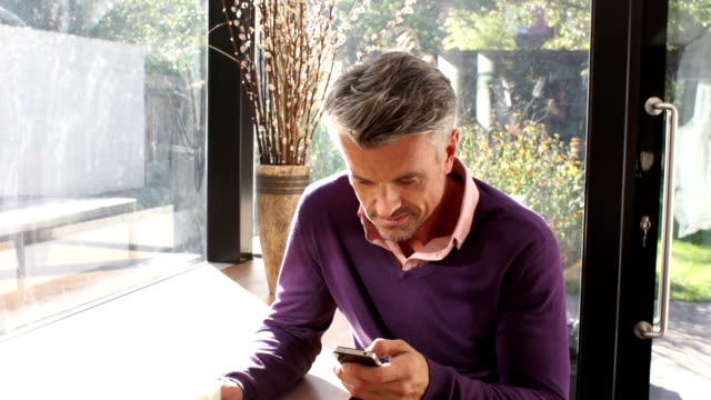 Man Using a Smartphone in his home