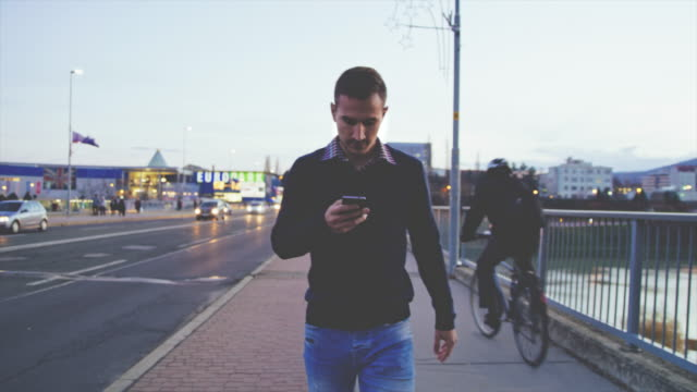 ws man using a smartphone while walking on sidewalk - carefree stock videos & royalty-free footage