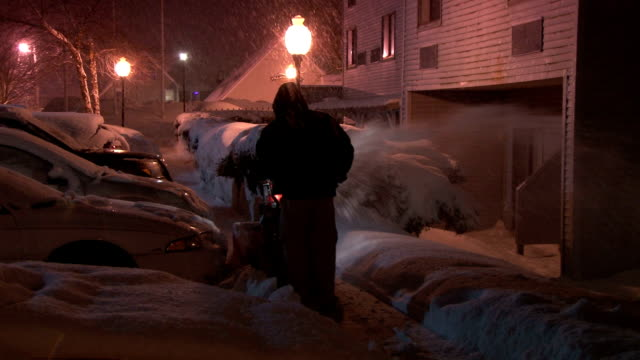 A man using a snow blower on a sidewalk as a blizzard takes aim at New England