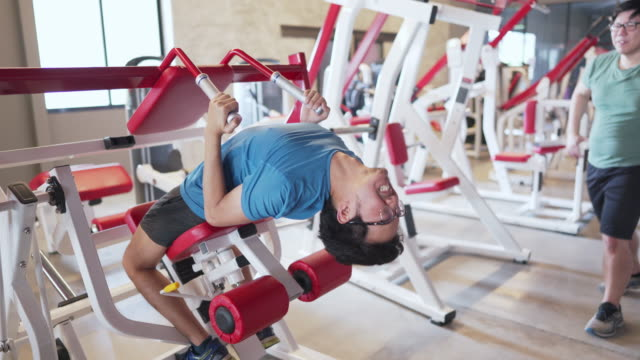 man using abdominal exercise machine the wrong way at the gym then his friend telling him. funny comedy concept - slim stock videos & royalty-free footage