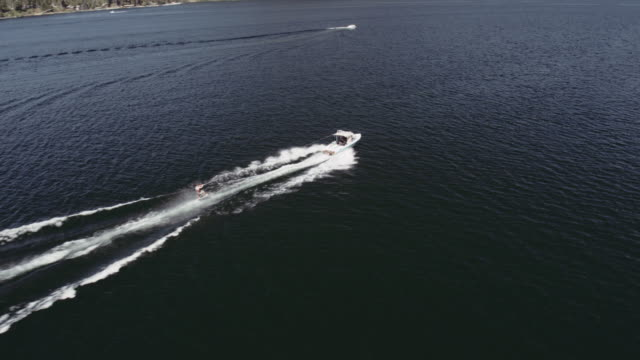4k aerial: man using air chair behind a boat - motorboat stock videos & royalty-free footage