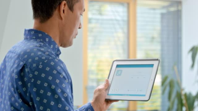 彼のスマート ホームのパラメーターを調整する彼のタブレットのアプリを使用して ds 人 - セレクティブフォーカス点の映像素材/bロール