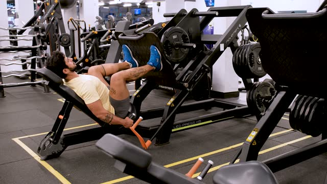 man using apparatus to strengthen his legs in gym - effort stock videos & royalty-free footage