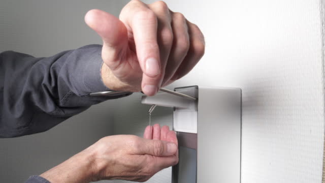 man using automatic hand sanitizer dispenser - soap dispenser stock videos & royalty-free footage