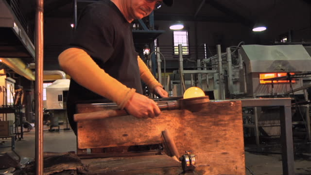 MS Man using blocking tool to form and smooth molten glass at glass blowing factory / Windsor, Vermont, USA