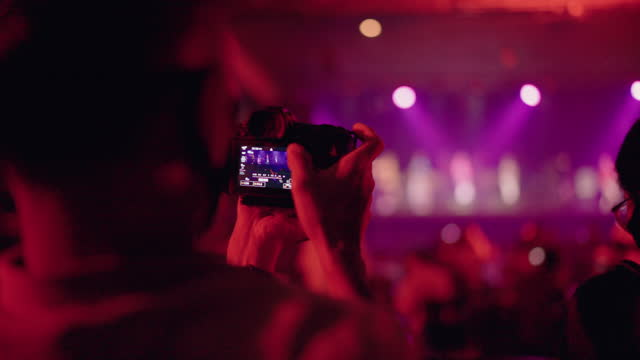 man using camera recording concert while asian band performing a concert on stage. - photography themes stock videos & royalty-free footage